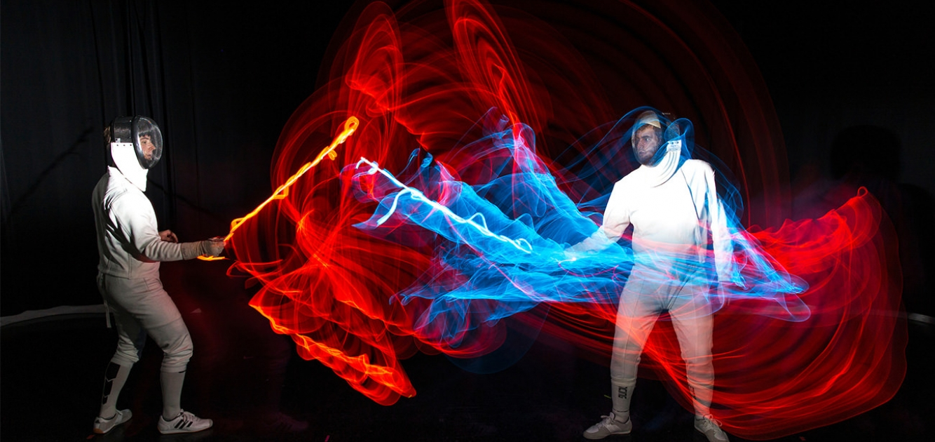 2 students fencing with colored lights attached to their sabres