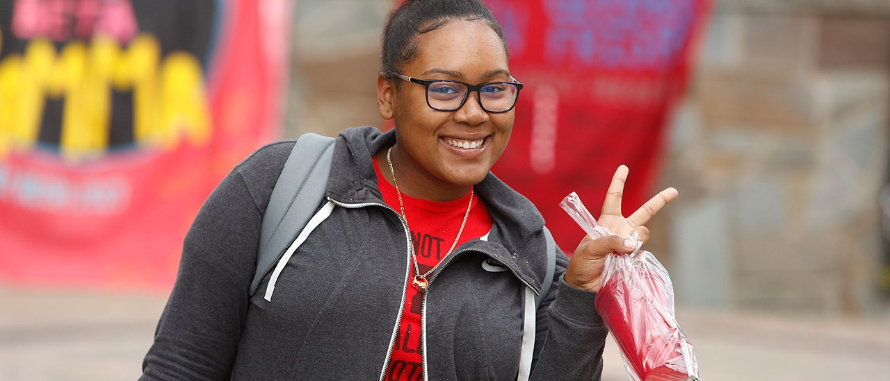 Girl gives peace sign at Red Day