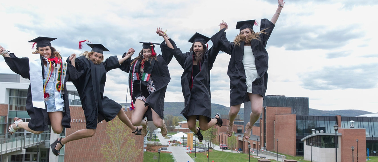 Friends jump and hold hands on graduation day
