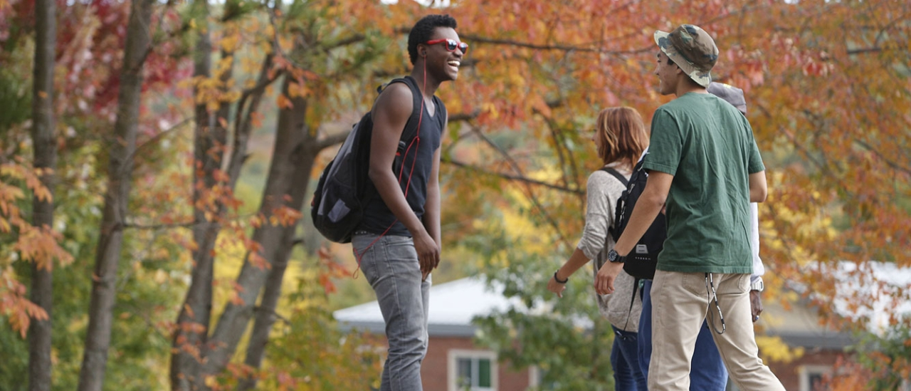 Students talking while walking around campus on a Fall day.