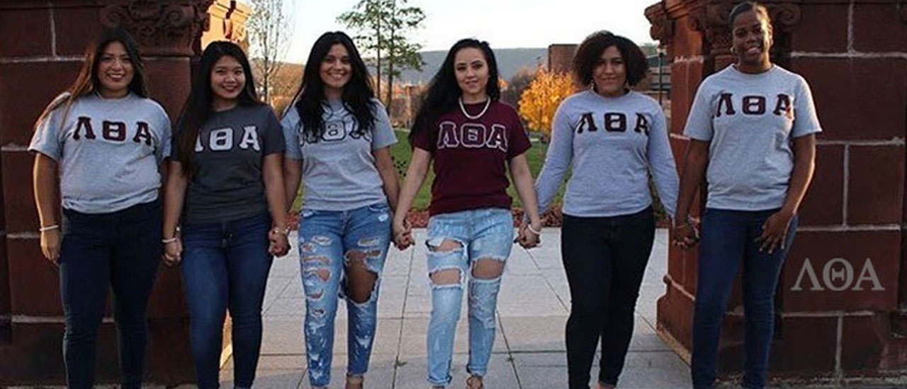 Girls in the Lambda Theta Alpha sorority standing in front of the pillars.