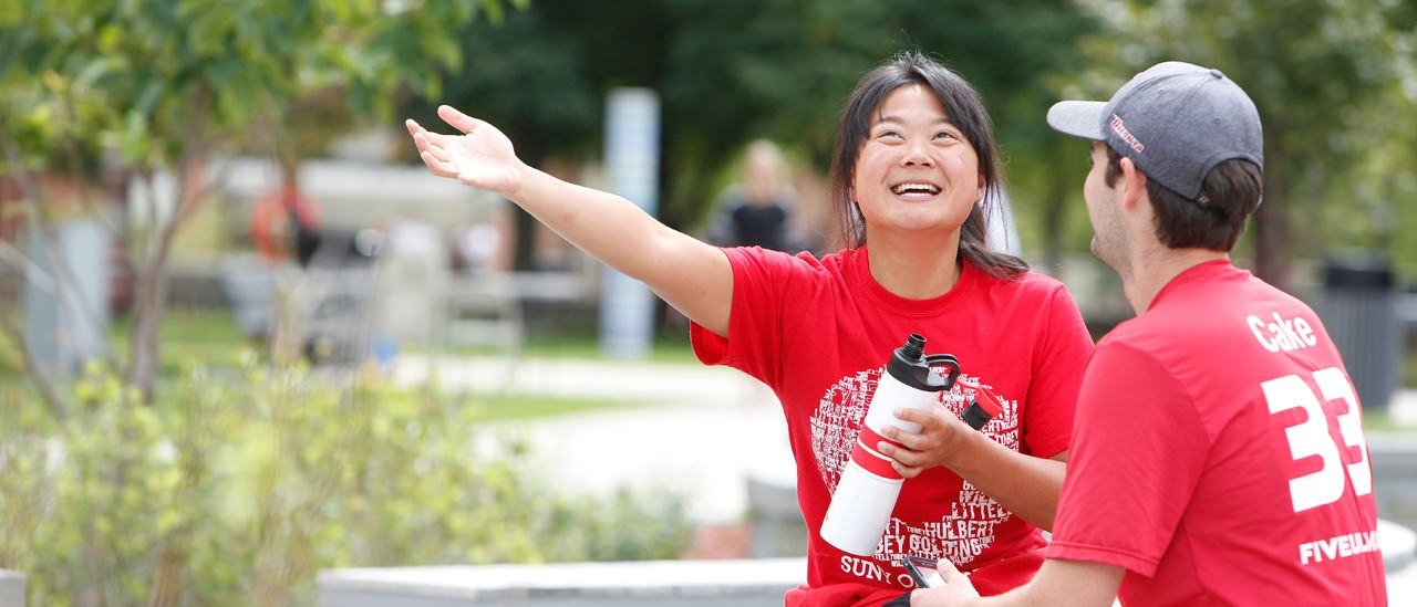 Students having a conversation wearing red day shirts in the quad