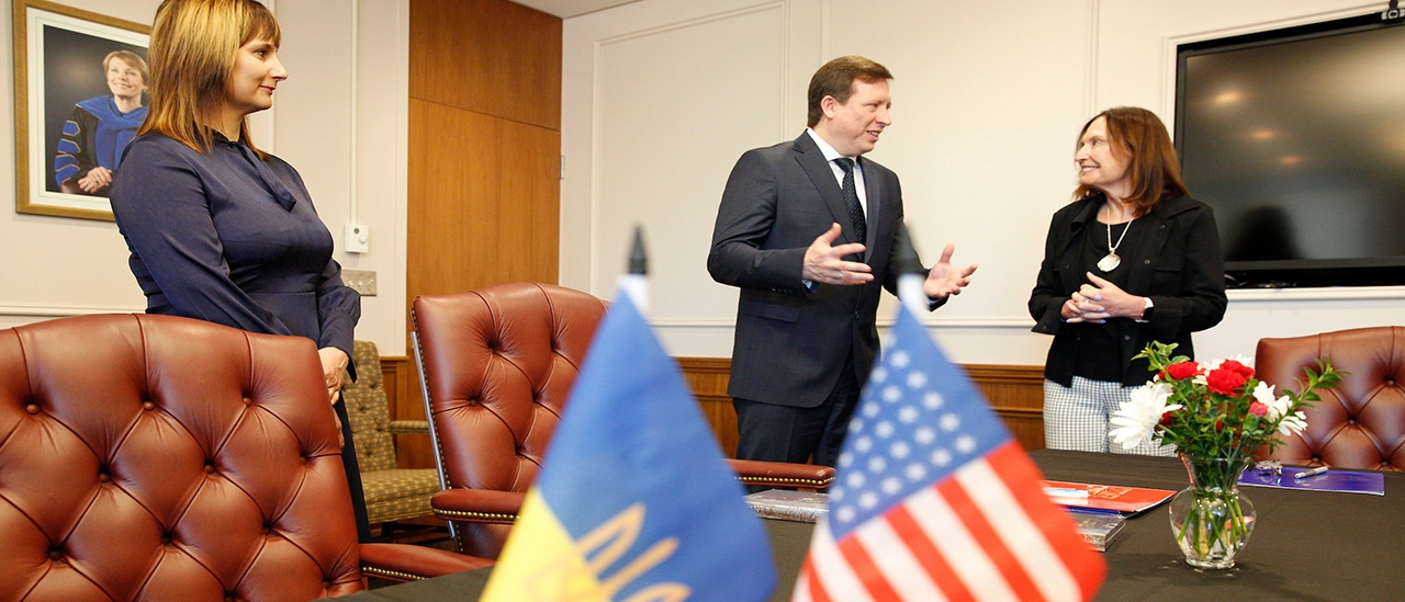 President Morris talks to a representative from Ukraine, with the American and Ukrainian flags in the foreground