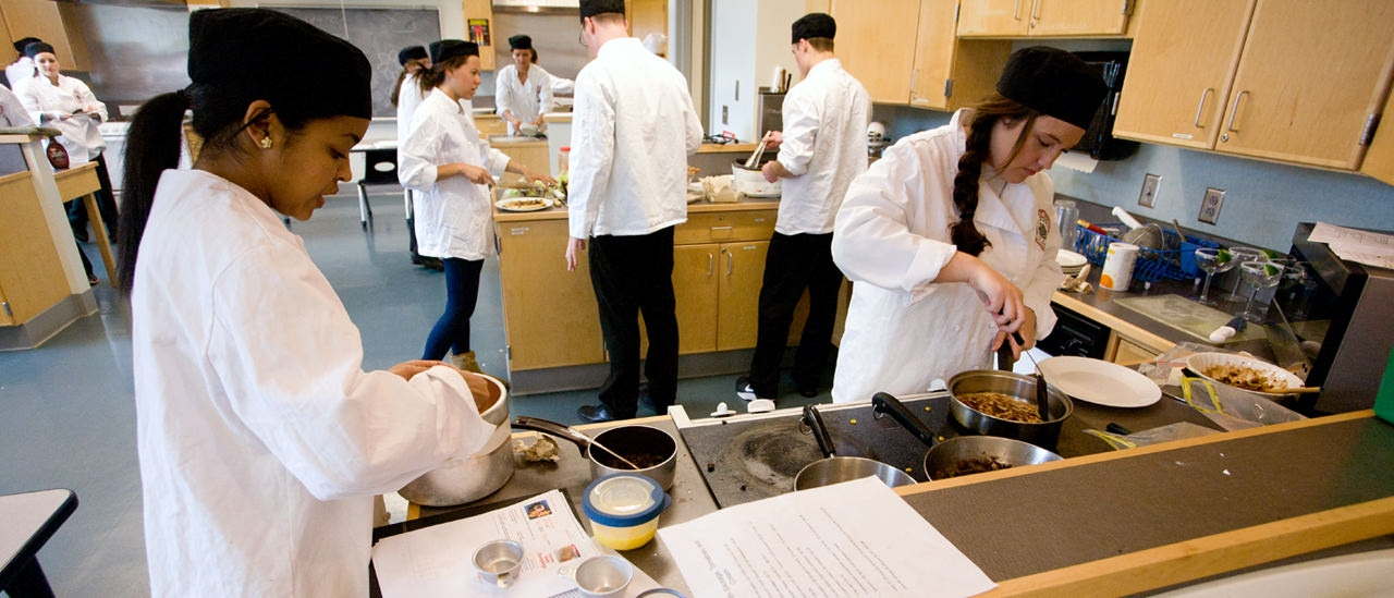 Students practicing recipes in the college kitchen.