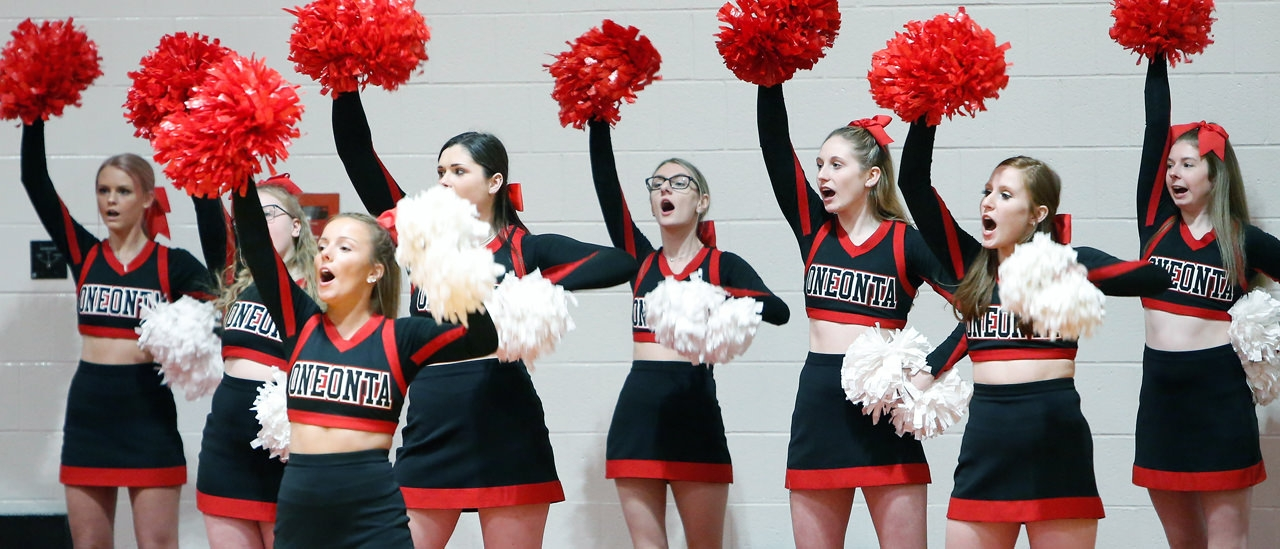 Cheerleaders cheering on the basketball team.