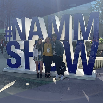 three students in front of NAMM Show sign