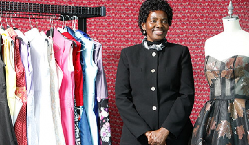 Annacleta Chiweshe stands between a rack of dresses and a dress form