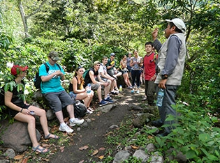 Students and faculty on a bench in a Guatemalan forest.