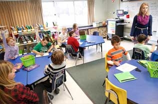 Student teaching children in a classroom.