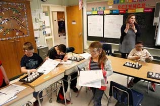 Children drawing with a student teaching them.