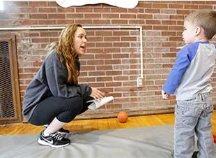 Female student crouching to talk to a little boy.