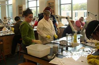 Students testing different fabrics in a lab.