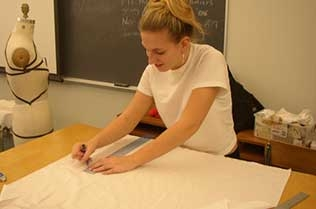 Student using a ruler to measure out a piece of fabric.