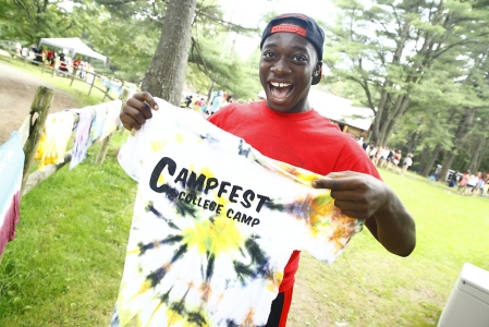 Man holding up a tye-die shirt that says CampFest on it.