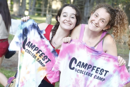 Two girls holding up tye-die shirts that say Campfest on them.