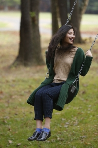 Girl swinging on a swing in a forest.