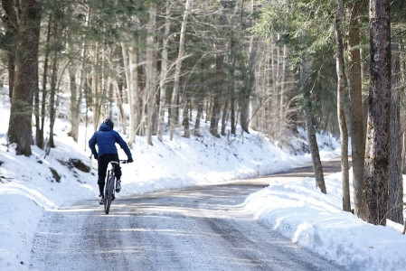 Person riding a bike on a snowy road.