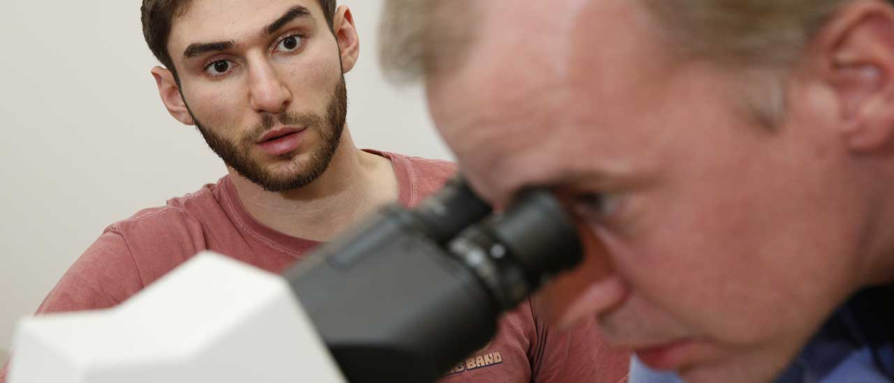 Dr. Florian Reyda looks through a microscope