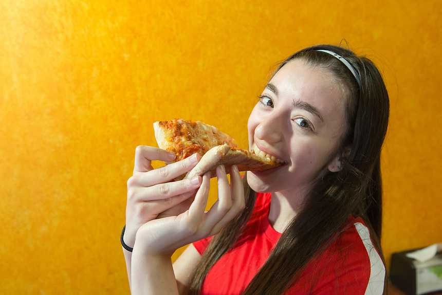 Student biting into a slice of pizza