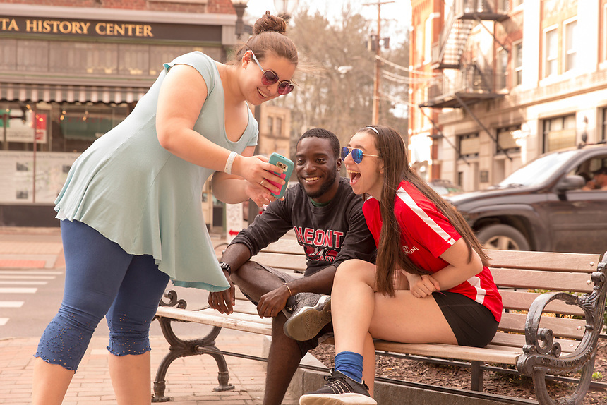 Woman showing her phone to two students laughing.