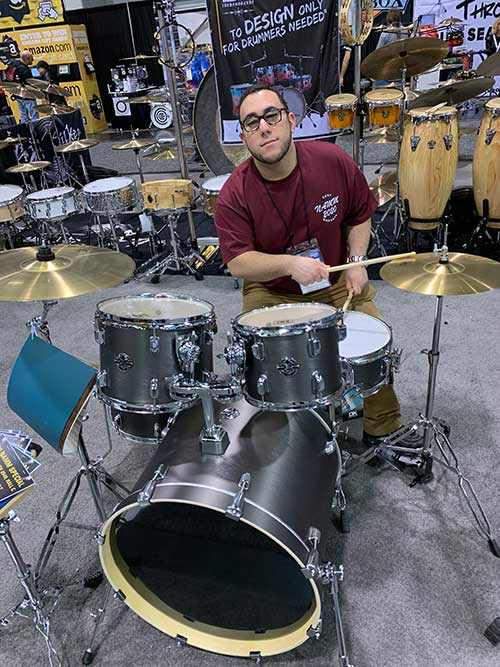 Ryan Mastrelli tests out a drum set.