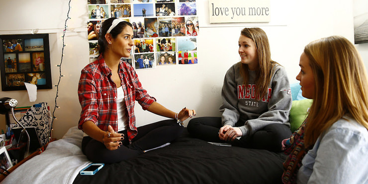 Female students sitting on their dorm room bed talking.